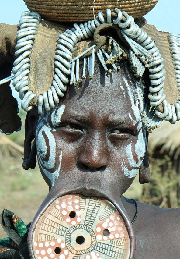 Женщина из племени Мурси с традиционной тарелкой Дэби в нижней губе, которая является символом красоты. Племя проживает на юге Эфиопии в национальном парке Маго.