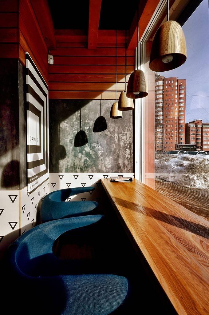 Полы выполнены в двух цветах : бетонный графит и тиковое дерево – разделяя залы на 2 разных зоны. Потолки дополнили объёмными балками в цвет пола – задав ритм в небольшом пространстве, который начал «работать» после монтажа освещения.